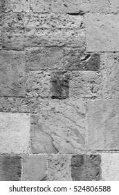 Ancient italian sandstone church wall vertical closeup black and white texture