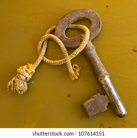 Ancient key on grunge metal background Old rusty key tied with frayed string isolated on grungy metal background.