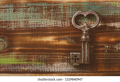 Ancient key. Retro background. Wooden surface painted. The texture of wood, strokes of colored paints. Empty space. Aged creative wooden background