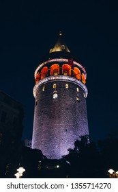 Ancient landmark Galata tower lit by lights in the evening. Beyoglu, Istanbul, Turkey.