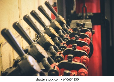 Ancient levers on a control panel machine in a factory
