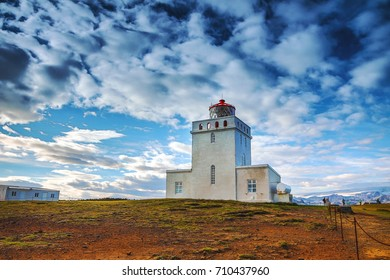 Ancient lighthouse on rock and evening Icelandic landscape.