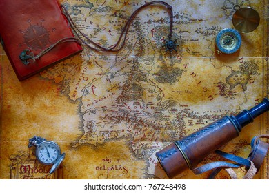 Ancient map (possibly pirate or treasure or middle-earth) with adventure attributes stuff (compass, notepad, telescope and pocket watch) around the perimeter
