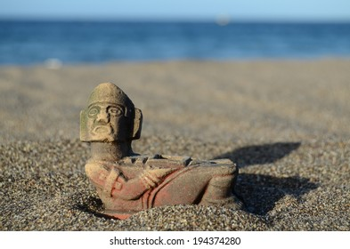 Ancient Maya Statue on the Sand Beach near the Ocean