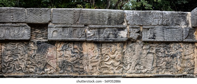 Ancient Mayan mural depicting an eagle grasping a human heart and a warrior holding a human head on the Platform of the Skulls, a.k.a. Tzompantli in Chichen Itza, Yucatan, Mexico