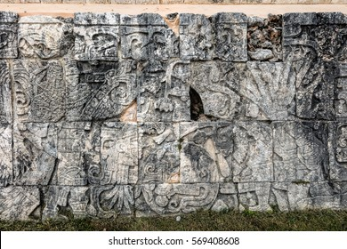 Ancient Mayan mural at the Great Ball Court in Chichen Itza depicting a player holding a knife  and a severed head in another. Opposite him a headless body with the snakes streaming out of the neck.