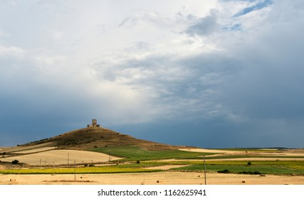 Ancient medieval castle in ruins of Spain on the hill and cultivated fields of sunflowers