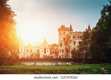 Ancient Medieval Castle or Stronghold with turrets and towers among green forest at sunset light, toned