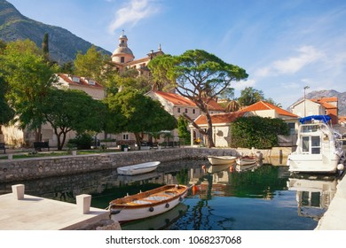 Ancient Mediterranean town of Prcanj on sunny autumn day. Montenegro, Bay of Kotor, view of small harbor for fishing boats and Birth of Our Lady Church