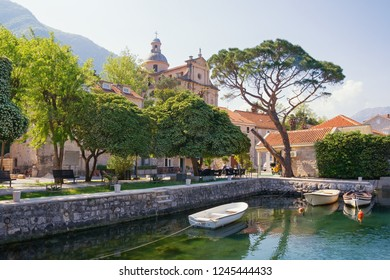 Ancient Mediterranean town of Prcanj on sunny spring day. Montenegro, Bay of Kotor, view of small harbor for fishing boats and Birth of Our Lady Church