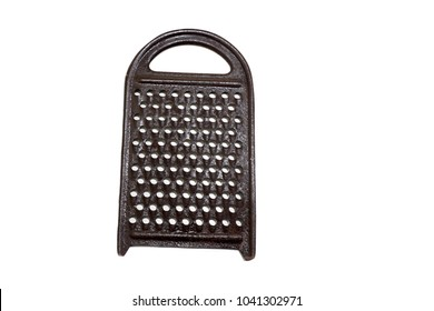 Ancient metal hand grater for vegetables. Retro vintage folk kitchen accessories. Manual iron, darkened from time grater for food, cheese, vegetables and fruits. Old working kitchen grater isolated