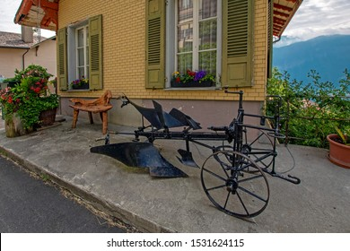 Ancient metal plow in front of cute house with beautiful flowers and wooden blinds in Beatenberg, Switzerland. Old times farming tool