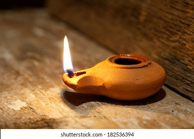 Ancient Middle Eastern oil lamp made in clay on wood table