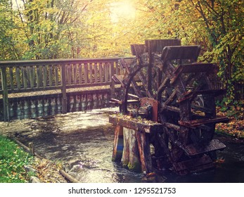 Ancient mill wheel in the running water of a river near a wooden bridge, soft focus, glowing light