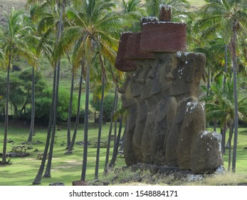 Ancient Moai statues on Easter Island surrounded by palmtrees.