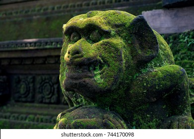 Ancient moss-grown statue of grinning monkey which is carved from the stone in the Ubud monkey forest, Bali, Indonesia