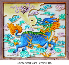 Ancient mystical oriental tablet with a Chinese mythological creature called Qilin flying amongst clouds. The creature is also known as Chinese Unicorn and brings good omen.