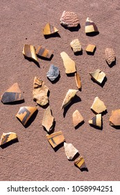 Ancient Native American pot sherds collected by visitors and arranged on a concrete sidewalk at Homolovi Ruins State Park in northern Arizona