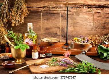 Ancient natural medicine. Herbs, vials and scale on wooden background