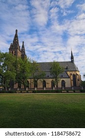"""Ancient Neo Gothic Church of Saint Peter and Paul in Vysehrad (""""Upper Castle""""). Summer landscape photo on a sunny morning. Prague, Czech Republic."""