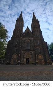 """Ancient Neo Gothic Church of Saint Peter and Paul in Vysehrad (""""Upper Castle""""). Summer landscape photo on a sunny morning. Selective focus with wide angle view. Prague, Czech Republic."""