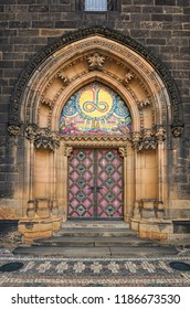 """Ancient Neo Gothic Church of Saint Peter and Paul in Vysehrad (""""Upper Castle""""). Ornamented entrance doors to Basilica. Prague, Czech Republic."""