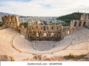 Ancient Odeon of Herodes Atticus in Athens, Greece on Acropolis hill with view over the city, sunset light and selective focus