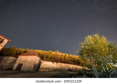 an ancient old building under the night sky, many stars and warm summer weather