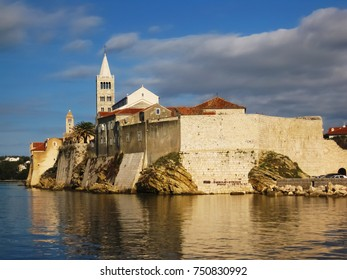 An ancient, old part of city Rab with its fortress and church by the shore
