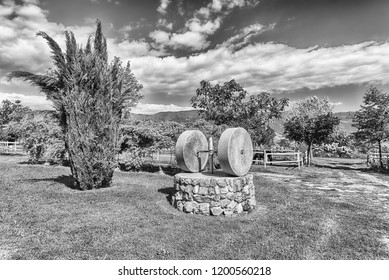 Ancient olive press with two millstones in the countryside