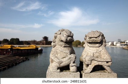 Ancient oriental stone carving of a pair of mythological creature known as Qilin, guarding an ancient Chinese wall city.