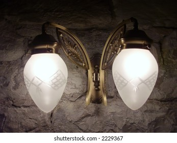 Ancient pair of lamps on stone wall detail