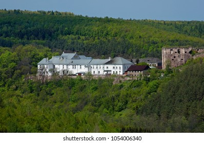 Ancient palace in the background of trees and mountains in Yazlivets, Khmelnytskyi region, Ukraine. Horizontal outdoors shot.