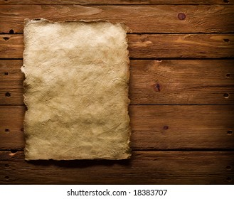 An ancient paper with torn edges, on a brown wooden surface.