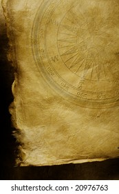 An ancient paper with torn edges, on a dark surface.