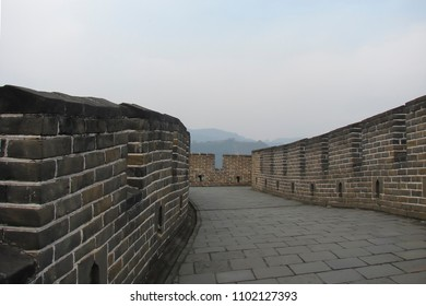 ancient paved road along the gray stonework parapet with gaps and loopholes, open corridor of the Great Wall of China in morning haze