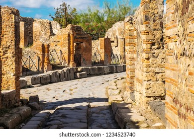 Ancient paved street is recovered in the middle of Roman ruins in Pompeii, Italy