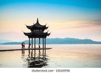 ancient pavilion reflection in the west lake at hangzhou with sunset glow,China