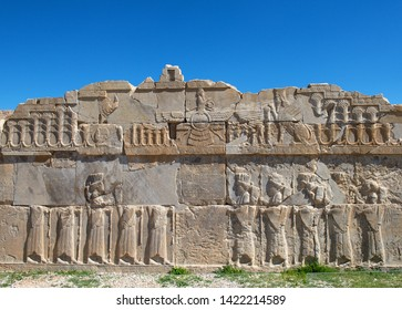 Ancient Persian ambassadors. Bearded men facing each other and holding hands.An ancient relief on the walls of the ruined Persepolis city.Persepolis is the capital of the ancient Achaemenid kingdom