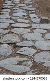 ancient piece of Roman road on the streets of Rome near the Colosseum showing the flagstones