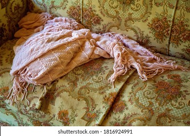 An ancient pink shawl lying abandoned on a vintage brocade chair from days gone by