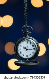 Ancient pocket watch with blurry light bokeh background