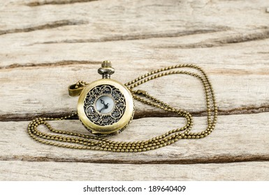 Ancient pocket watch and necklace isolated on old wooden  background.