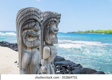 Ancient Polynesian style tiki wooden carvings along the beach greet visitors (tourists) to Ki'i Pu'uhonua O Honaunau National Park on the Big Island of Hawaii, an historic travel destination.