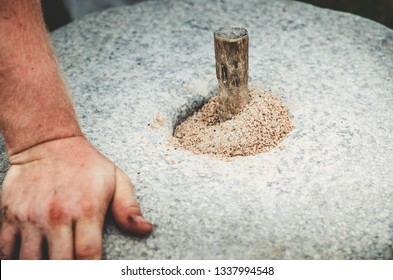 The ancient quern stone hand mill with grain close up. The man grinds the grain into flour with the help of a millstone. Men's hands on a millstone. Old grinding stones turned by hands