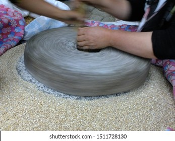 The ancient quern stone hand mill with grain. The man grinds the grain into flour with the help of a millstone. Women's hands on a millstone. Old grinding stones turned by hands