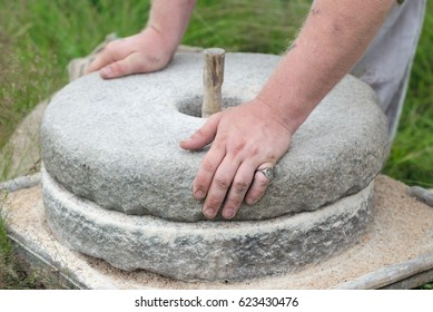 The ancient Quern stone hand mill with grain. The man grinds the grain into flour with the help of a millstone. Men's hands on a millstone. Old grinding stones turned by hands