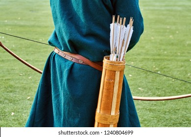 Ancient quiver with arrows on the medieval archer's back on the green grass background