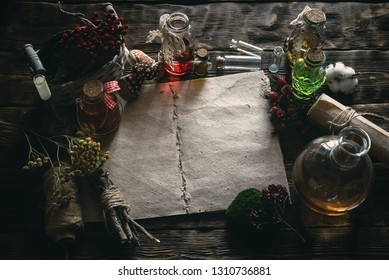 Ancient recipe scroll book and various dry herbs on a table of witch doctor. Herbal medicine essential oil on a table. Witchcraft background with copy space.