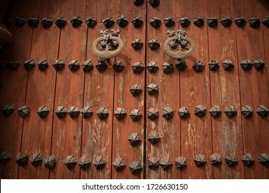 ancient red wooden door with metallic ornaments